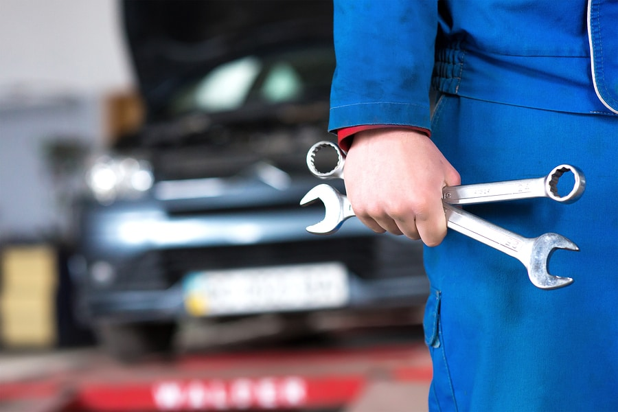 Car mechanic holding spanners